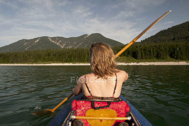 Rear view of woman paddling canoe over mountain range on background — Stock Photo