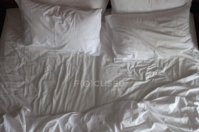 Top view of unmade double bed — Stock Photo