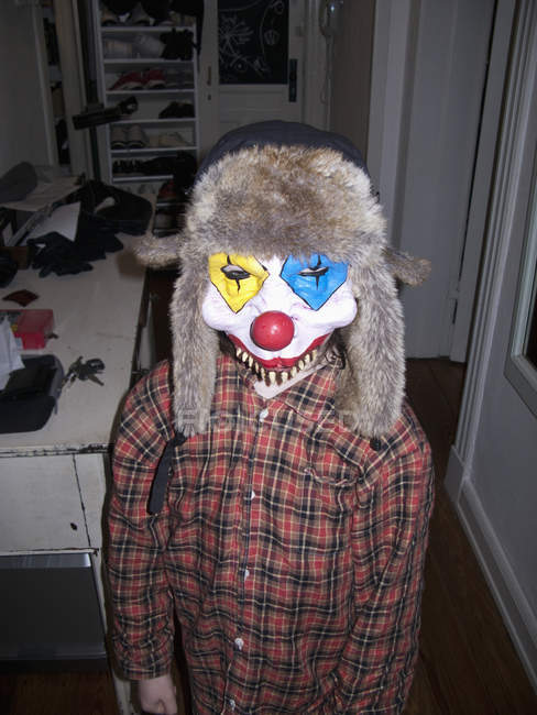 Portrait of kid wearing scary clown mask at home — Stock Photo