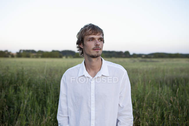 Young man in white shirt standing in field and looking away — Stock Photo