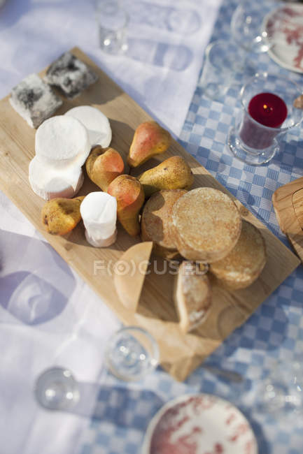 Top view of cheeses on chopping board sitting on table outside among glasses. — Stock Photo
