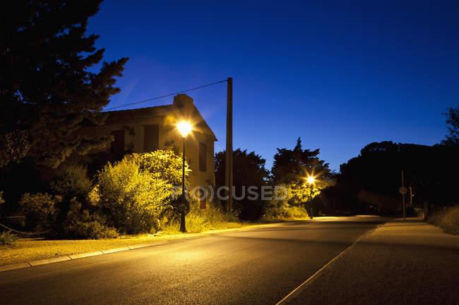 Просмотр фонарей горит жилой улице в сумерках — стоковое фото