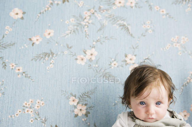 Портрет ребенка перед цветочными обоями — стоковое фото