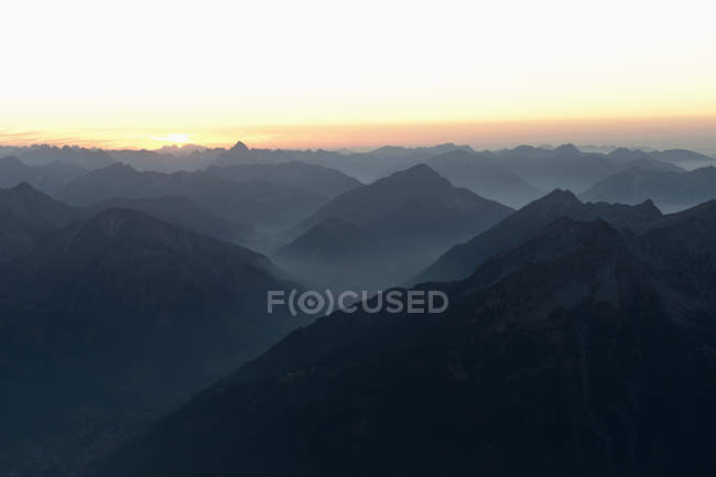 Scenic landscape of foggy mountain range over pastel sunset sky — Stock Photo