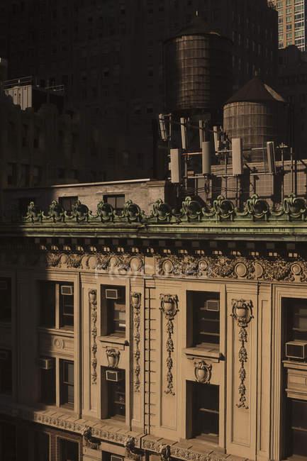 Tanques de armazenamento de água de madeira antiquados no telhado do prédio de apartamentos de luxo — Fotografia de Stock