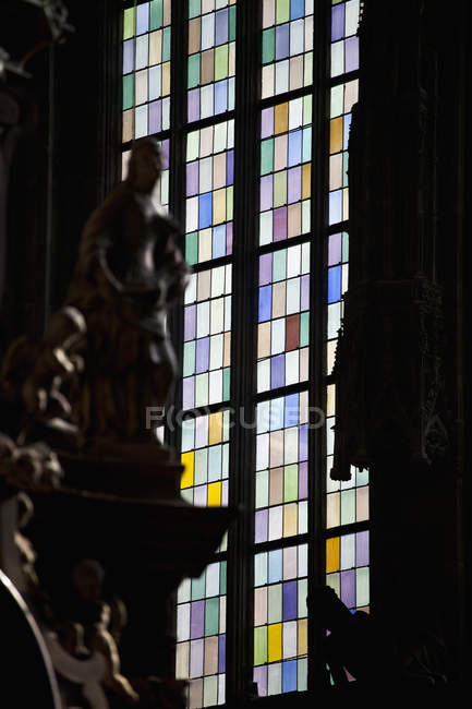 Carved statues over stained glass window on backdrop — Stockfoto