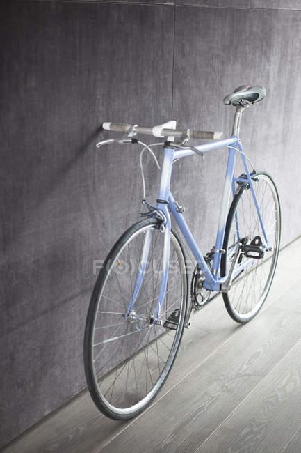 Bicicleta vintage inclinada na parede cinza . — Fotografia de Stock