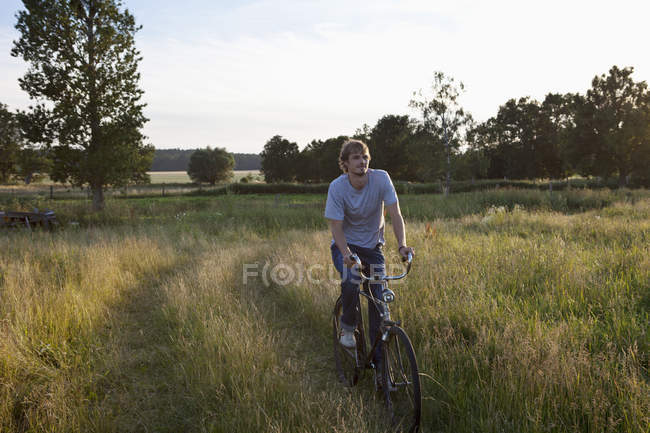 Young man riding bicycle in field — Stock Photo