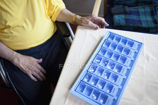 Ernte senior Mann sitzt im Rollstuhl neben wöchentlichen Pille Veranstalter — Stockfoto