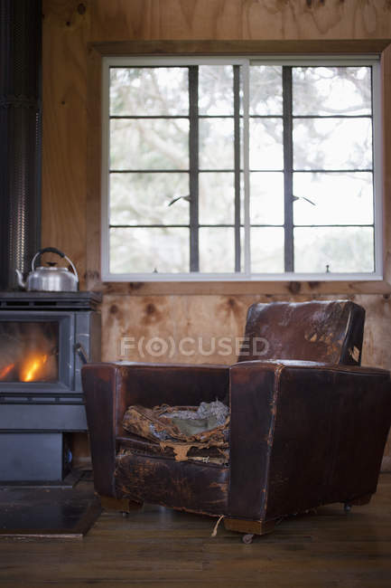 A well worn leather armchair beside wood burning stove — Stock Photo