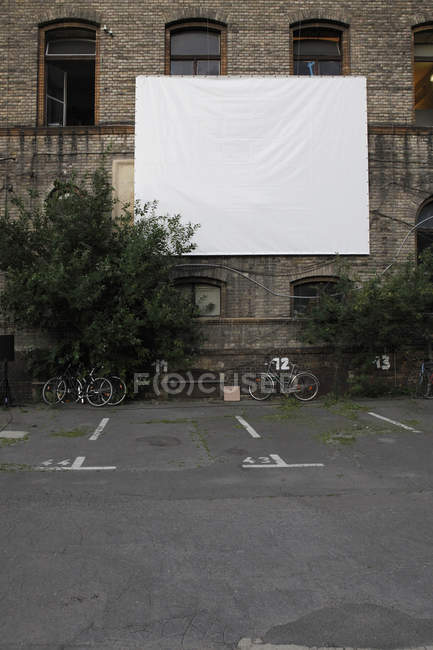 Projection screen on facade of Postfuhramt Building at empty car park — Stock Photo