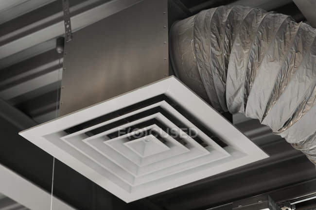Industrial air duct hanging at ceiling - foto de stock