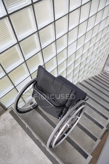 High angle view of wheelchair placed at top of stairs — Stock Photo