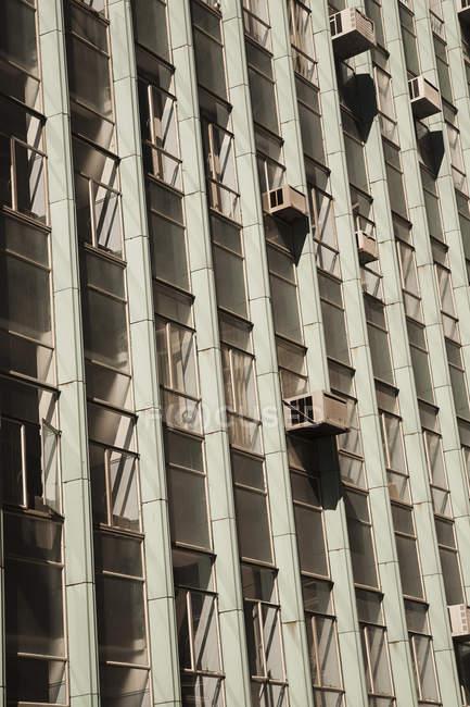 Fachada rascacielos con ventanas y aires acondicionados - foto de stock