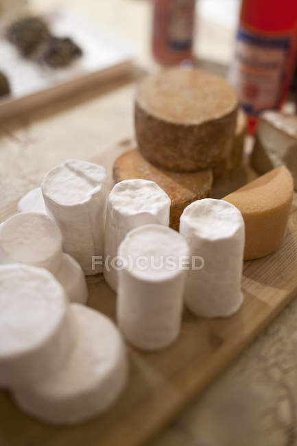 Close up view of wrapped cheeses on wooden chopping board on table — Stock Photo