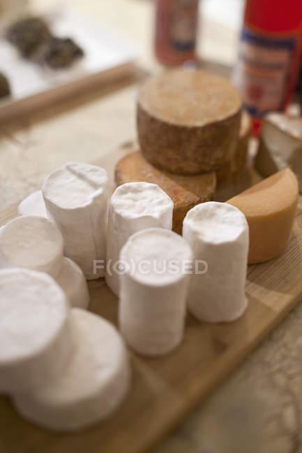 Nahaufnahme des verpackten Käse auf hölzernen Schneidebrett auf Tisch — Stockfoto