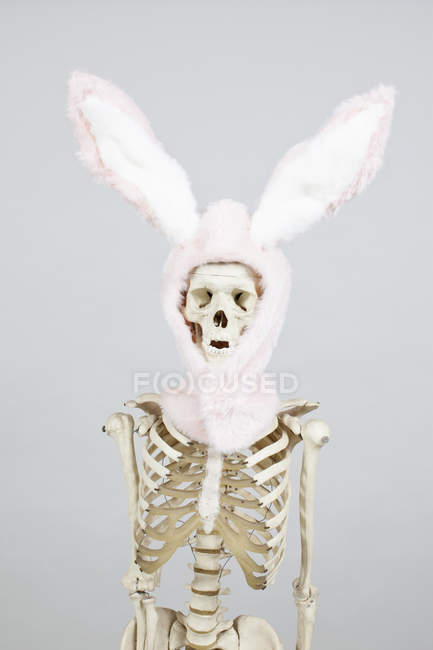 Skeleton in bunny ears hat over white wall on background — Stock Photo