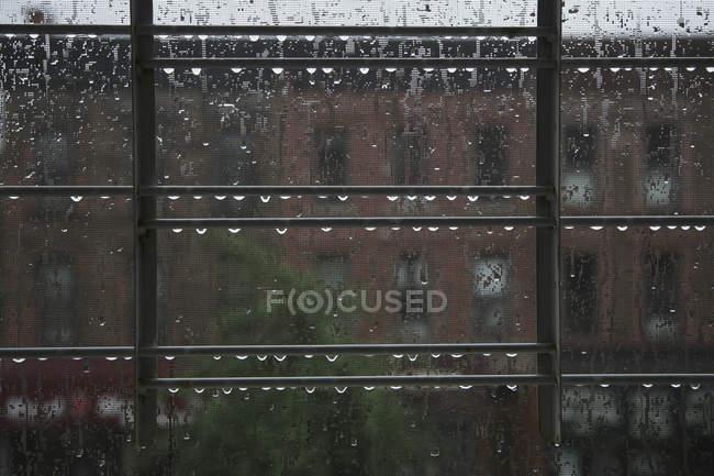 Gocce di pioggia sulle griglie dietro il vetro — Foto stock
