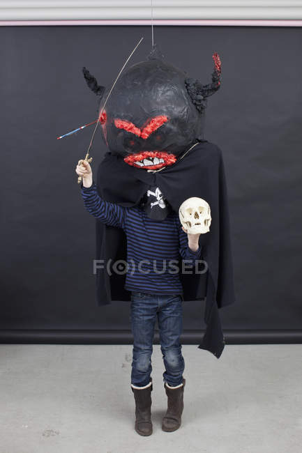 Kid wearing Halloween outfit posing with skull and toy sword in hands — Stock Photo