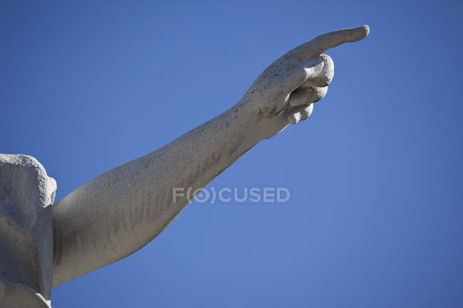 Crop statue hand pointing with finger over blue sky background — Photo de stock