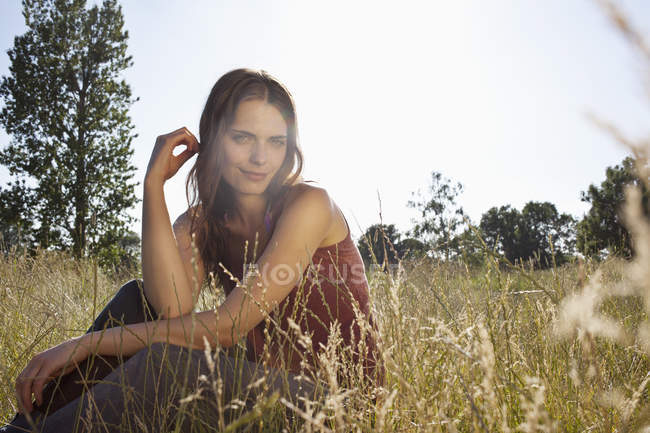 Young woman sitting amongst timothy grass in sunshine and playing with hair — Stock Photo