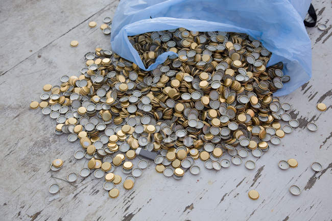 Pile of bottle caps spilling out of garbage bag — Stock Photo