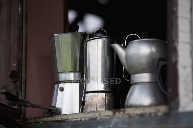 Three different espresso makers in row on window sill — Stock Photo