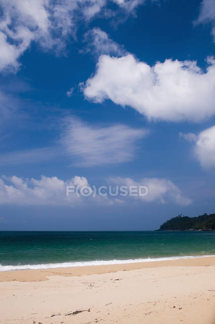 Scenic view of tropical beach on background of bright sky — стоковое фото