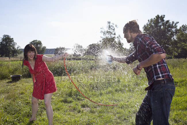 Young woman spraying man with hose on field — Stock Photo