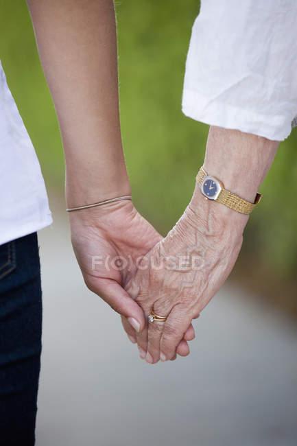 Crop senior e giovani donne che si tengono per mano — Foto stock