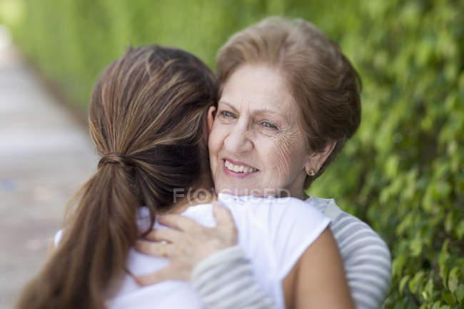 Старшая женщина обнимает внучку на улице — стоковое фото