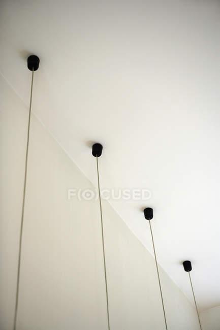 Quatre luminaires avec câbles suspendus au plafond — Photo de stock