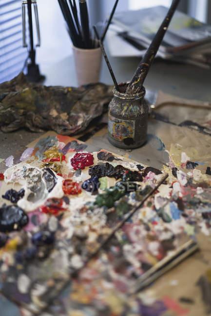 Pintura de aceite en paleta y pinceles en tarro - foto de stock