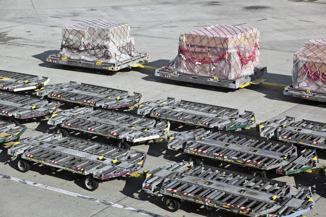 Empty baggage trailers and cargo on airport tarmac — Stock Photo