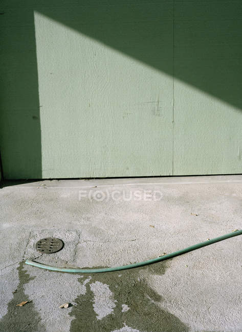 Garden hose on ground by green wall — Stock Photo