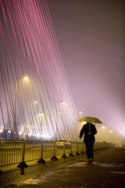 Человек с зонтиком во время прогулки по городской улице , — стоковое фото