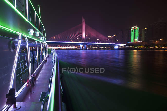 Yacht on Pearl River in Hong Kong with illuminated Haiyin Bridge in background — Stock Photo