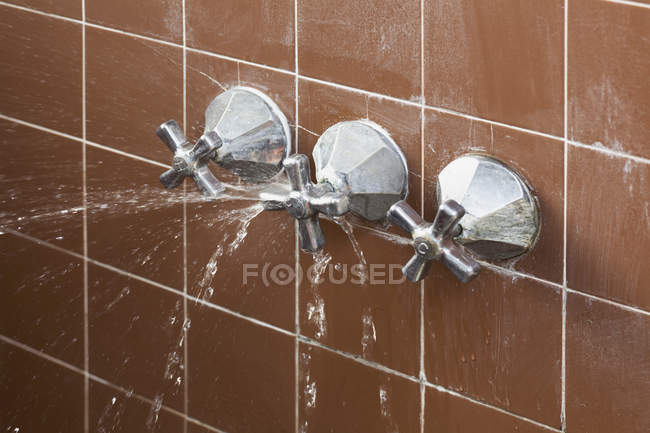 Broken shower faucet handle spraying leaking water — Stock Photo