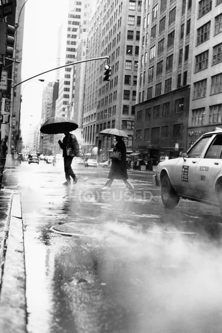 Pedoni con ombrelloni che camminano sul marciapiede della città — Foto stock