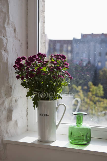 Green bottle and bouquet of flowers on window sill — Stock Photo