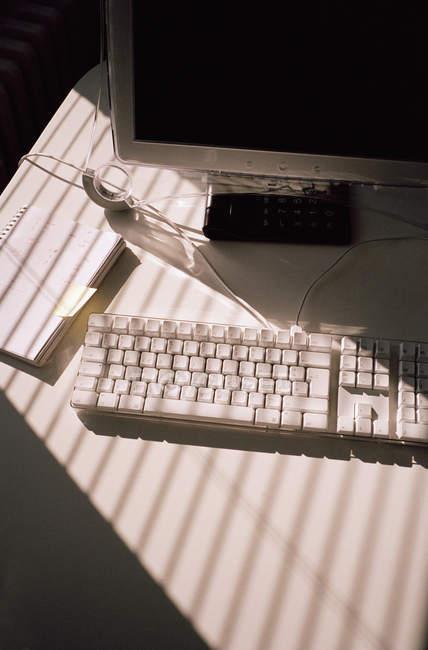 Ноутбук и монитор компьютера с клавиатурой на столе — стоковое фото