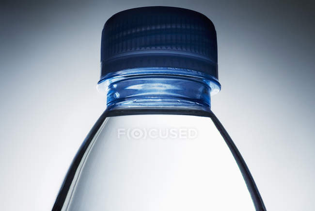 Close up of water bottle and cap over gradient grey backdrop — Stock Photo