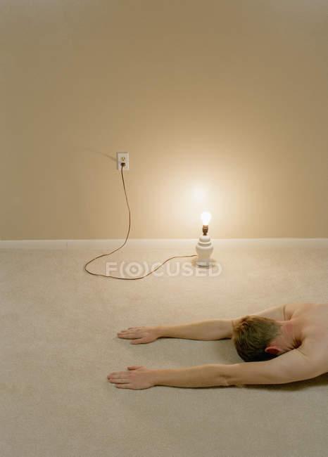 Crop uomo che si estende sul pavimento da lampada — Foto stock
