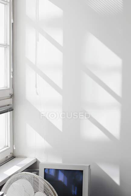 Контур окна, затененного на стене за вентилятором и монитором — стоковое фото