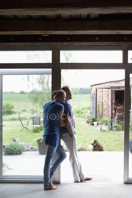 Um casal afetuoso, apoiando-se na entrada da sua casa — Fotografia de Stock