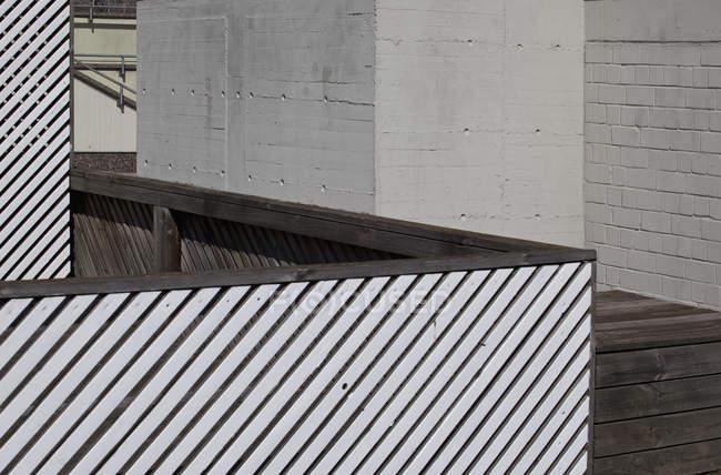 Fusion de formes de clôture à rayures, passerelle en bois et mur environnant — Photo de stock