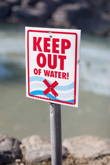 Keep Out of Water sign posted on rocky beach — Stock Photo