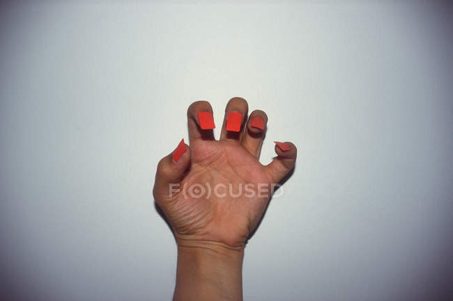 Crop hand with fake fingernails against white wall — Stock Photo