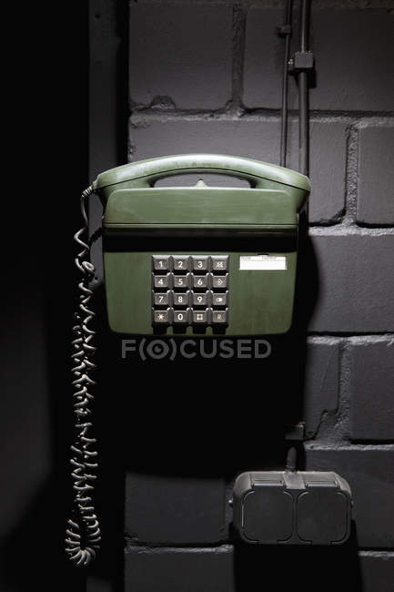 Green old-fashioned telephone on brick wall — Stock Photo
