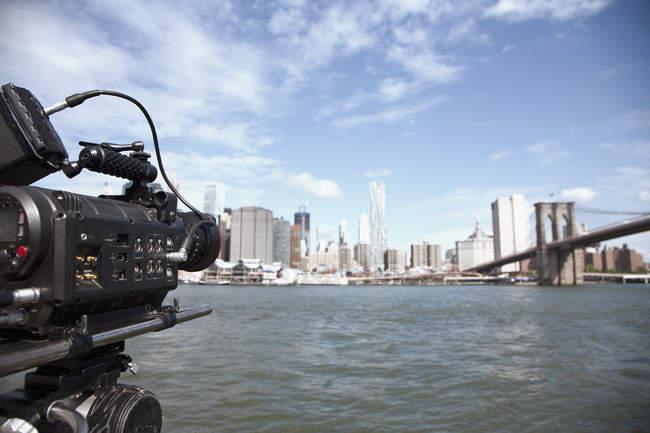 TV camera filming the Brooklyn Bridge and Manhattan skyline, New York City, USA — стоковое фото